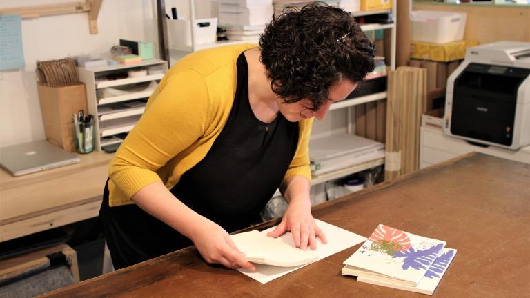 La designer réalise la reliure d'un carnet.